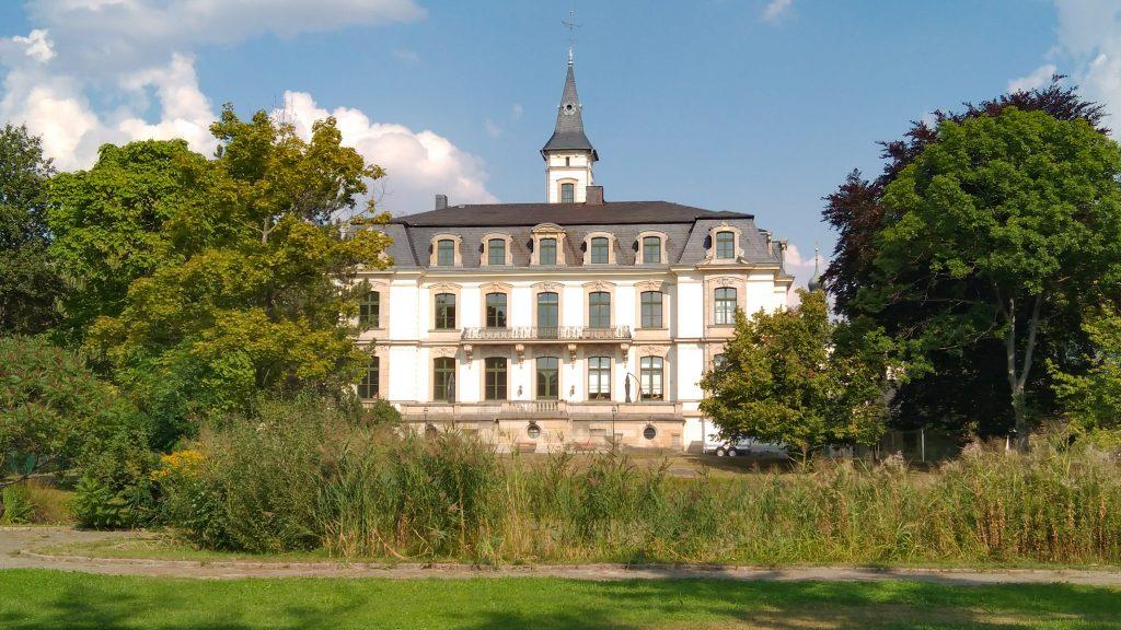 Schloss Schönefeld mit weißem Putz und Sandstein-Fenstereinfassungen mitten im Grünen