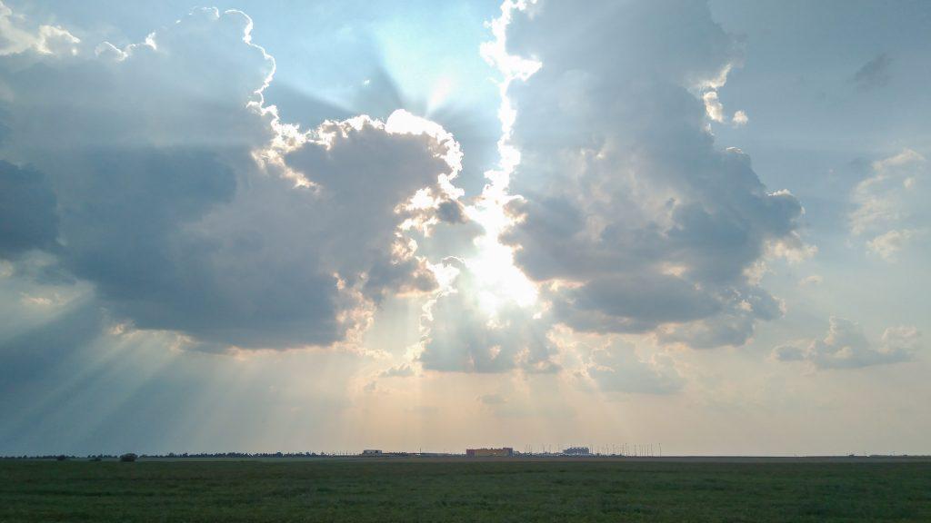 Eine rückseitig von der Sonne angestrahlte Wolkenformation über den entfernt liegenden Hallen von DHL