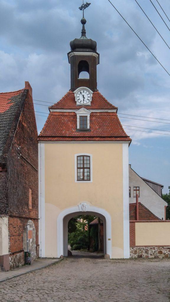 Eingangsportal in einem Turm mit Uhr