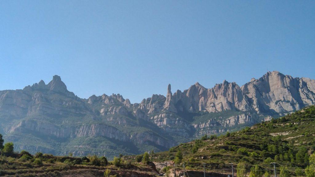 Panoramabild der Gebirgsketten Montserrat mit blauen Himmel dahinter und grünen Hügeln im Vordergrund