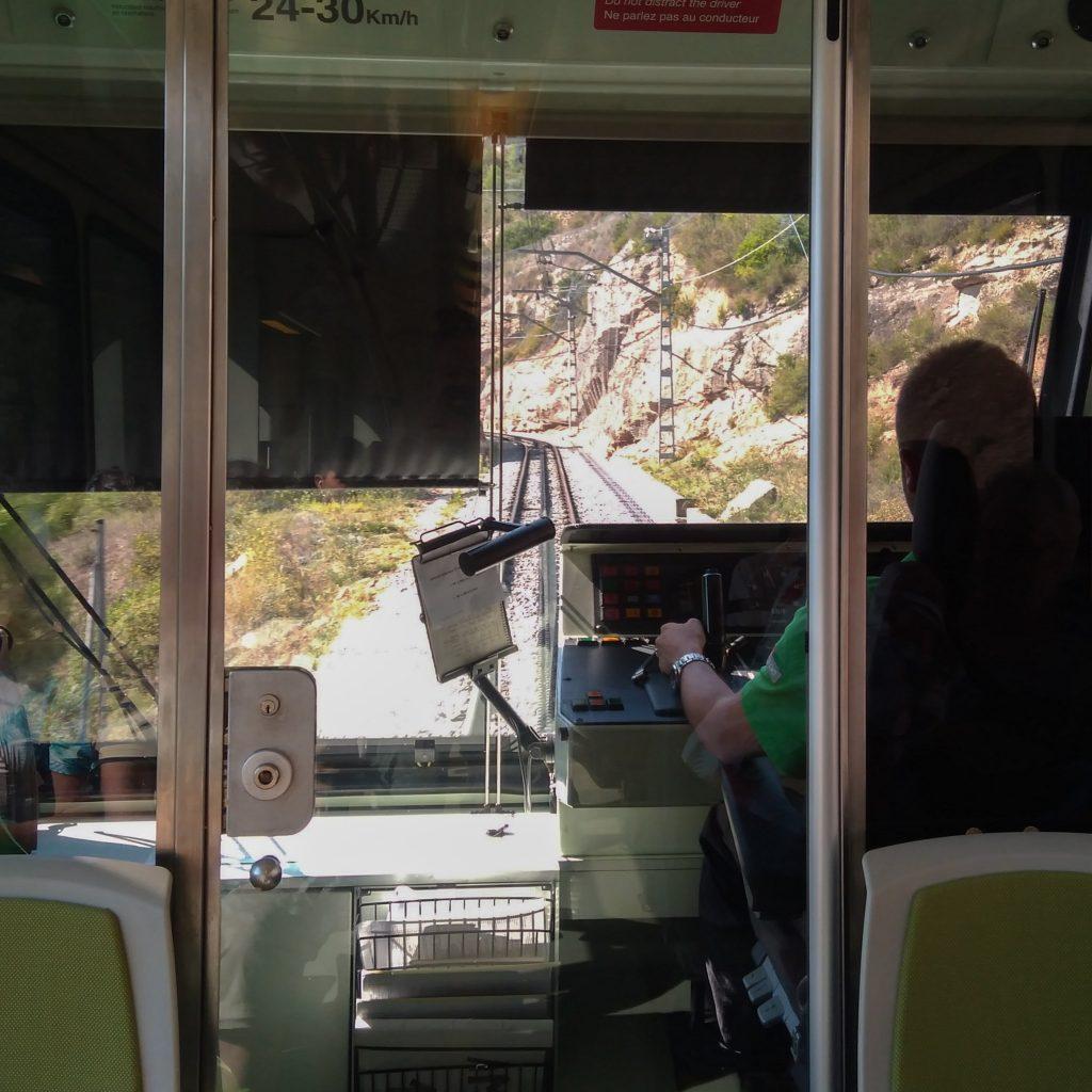 Der Blick durch das Führerhaus der Bergbahn auf die Schienen in Fahrtrichtung nach oben