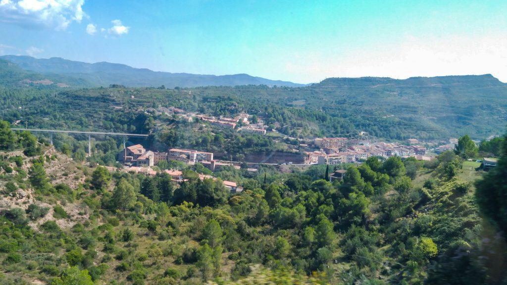 Blick aus der Bergbahn auf grüne Hügel und die Ansiedlung Monistrol de Montserrat