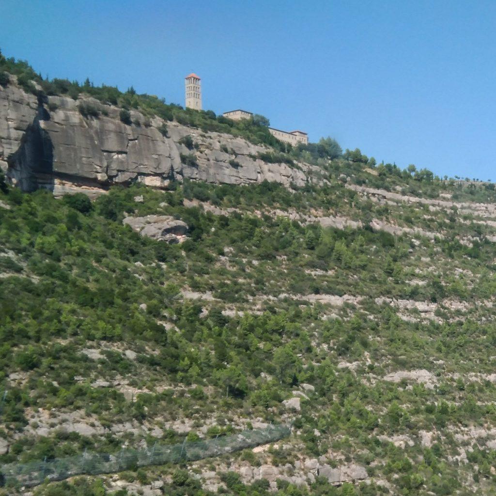 Blick aus der Bergbahn hinauf auf das Kloster Sant Benet de Montserrat auf einer Felskette
