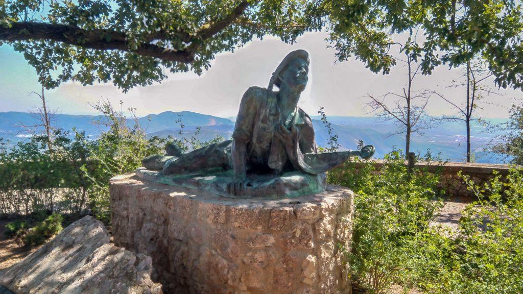 Bronze-Figur einer sich aufichtenden Person auf Steinsockel in einem Terassenahain