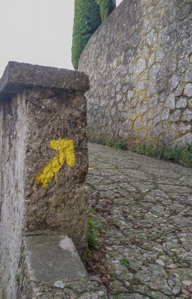 Weggabelung aus Natursteinpflaster mit gelber Pfeilmarkierung auf Mauervorsprung