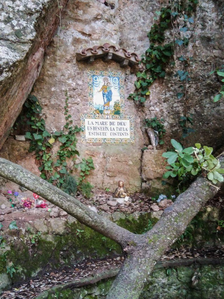 Umrankte Felsnische mit überdachtem, farbigen Gottesmutterbild auf Kacheln