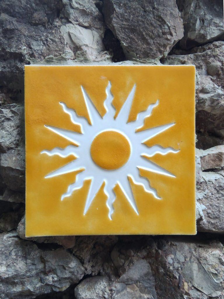 Gelb-weiße Sonnensymbol-Kachel als Wegemarkierung auf dem Felsen