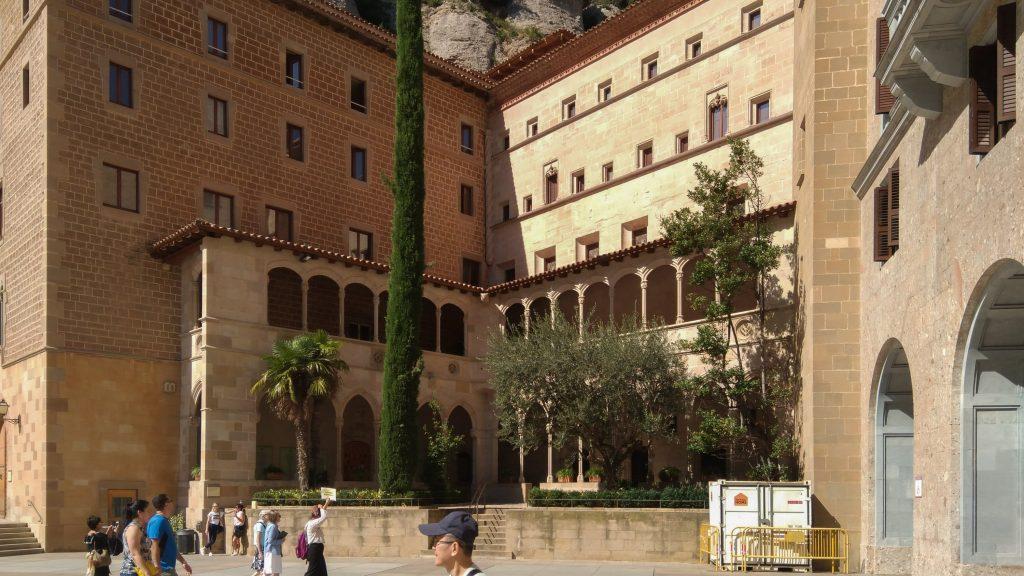 Gebäude-Innenhof-Ecke mit Säulengängen und Bepflanzung