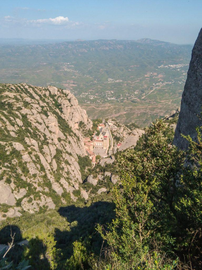 Blick von der Bergstation der Standseilbahn zum Kloster hinab, im Hintergurnd die Ebene vor den Bergen