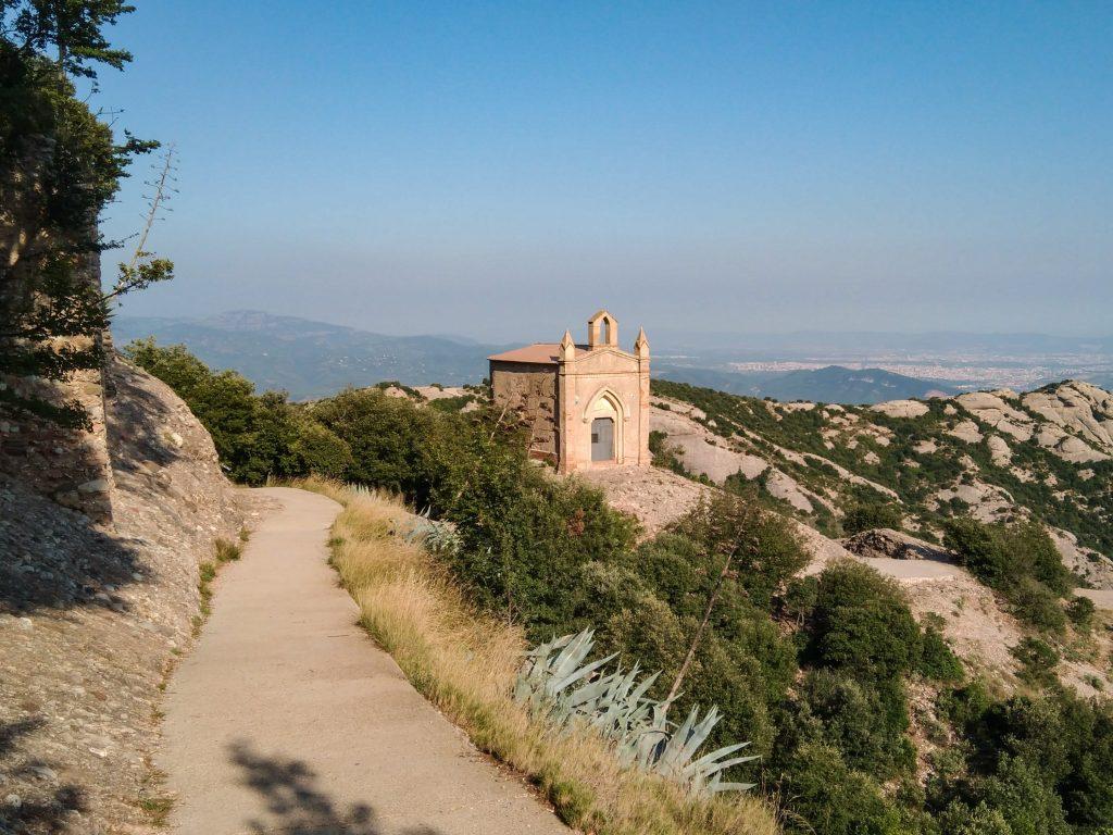 Kleine sandstein-Kapelle auf Felsvorsprung, im Hintergrund die ferne Landschaft