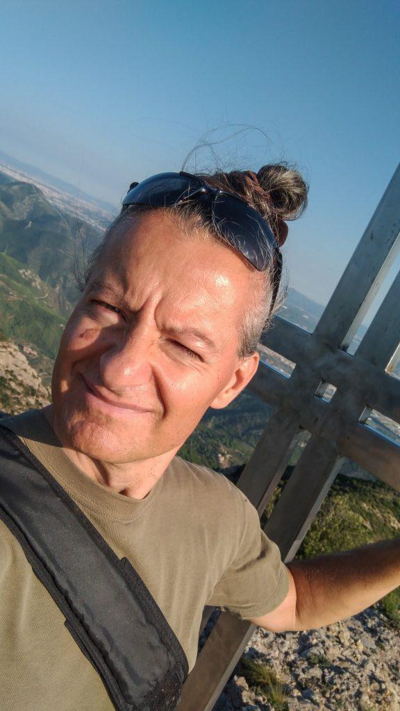 Portrait meines sonnegeblendeten Gesichtes am Gipfelkreuz mit Landschaft im Hintergrund