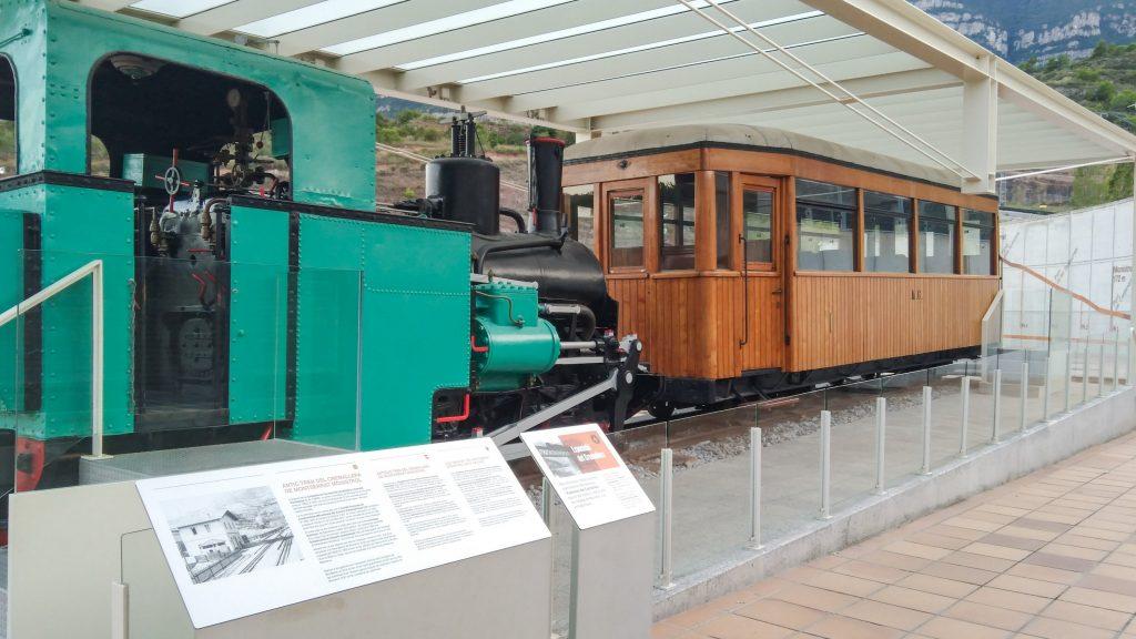Lok und Waggon der alten Zahnradbahn als Austellungstück auf dem Bahnhofsvorplatz