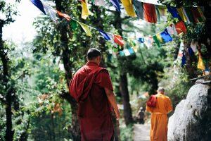 Zwei buddhistische Mönche auf Wanderschaft unter Gebetsflaggen