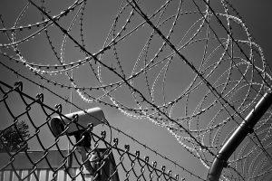 Schwarz/Weiß-Bild einer Überwachungskamera hinter Zaun und Stracheldraht
