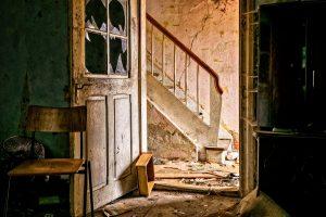 Blick aus einem verlassenen Raum in ein heruntergekommenes Treppenhaus